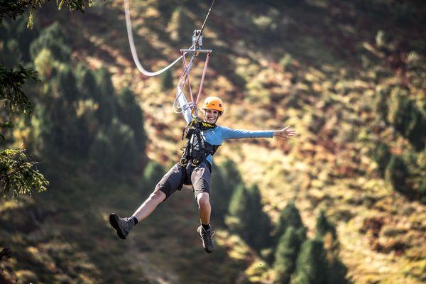 Frau fährt freudig auf dem Flying Fox