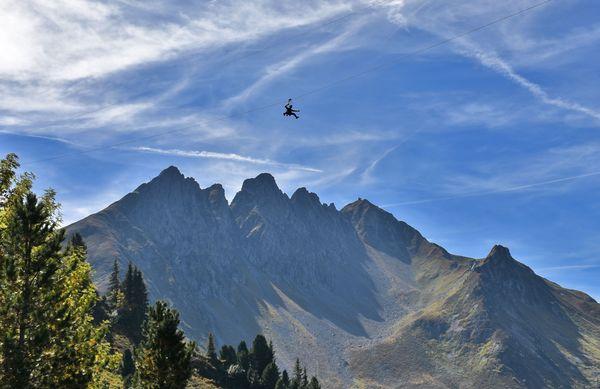 Person fährt mit dem Flying Fox über das Bergpanorama