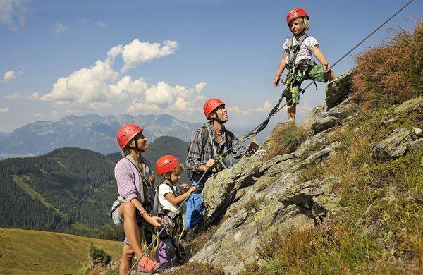 Familie klettert an Berghang